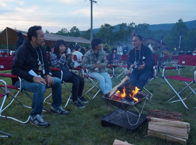 焚き火を囲んでユーザーと語らう山井社長(右)